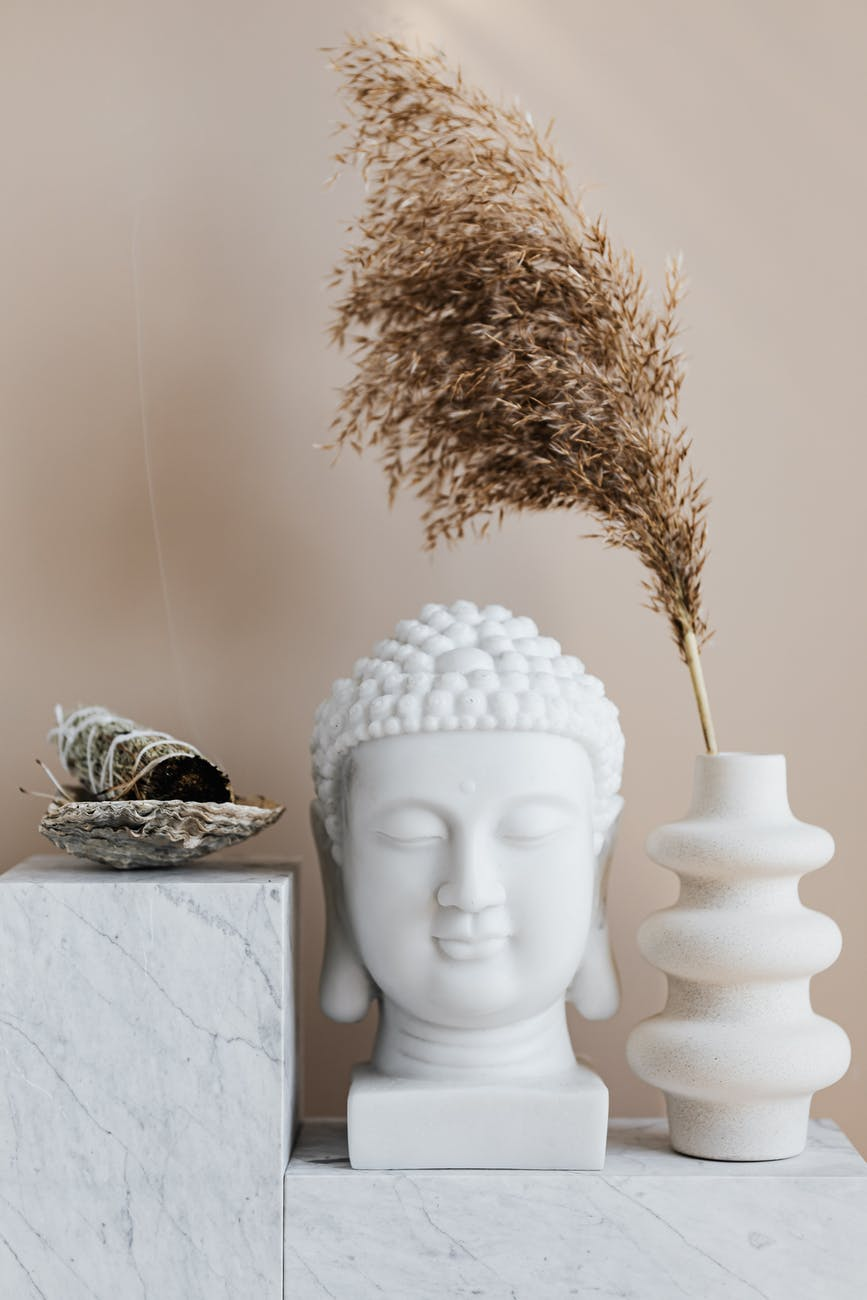 vase with dried herb arranged with buddha bust and sage smudge stick in bowl