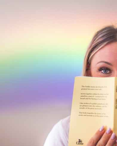 cheerful woman covering face with book