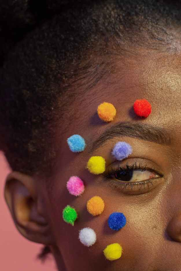 crop black woman with multicolored fluffy balls on face