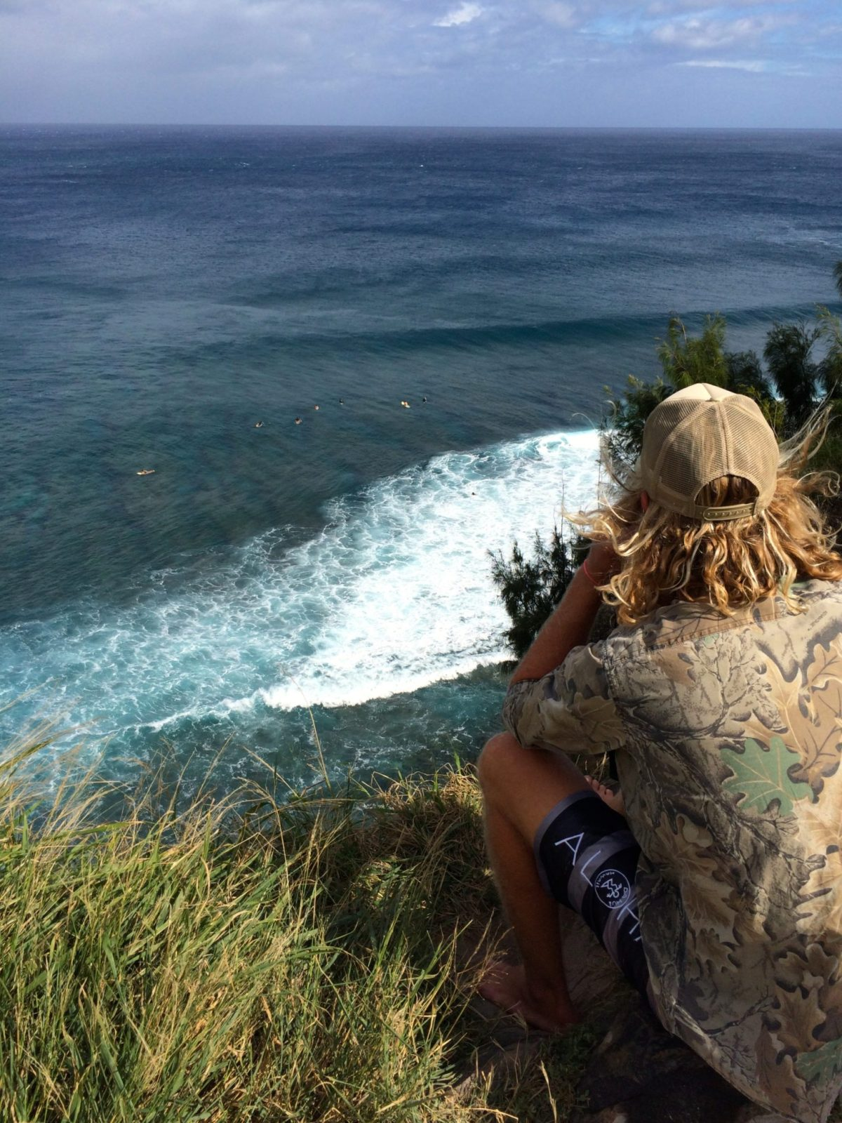 A surfer watching surfers at Honolua Bay, Maui.