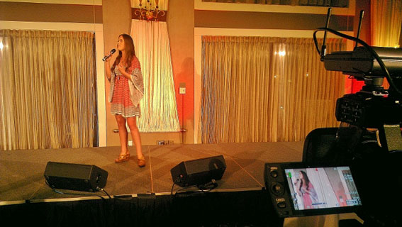 The camera frames up a North Shore Star singing contestant