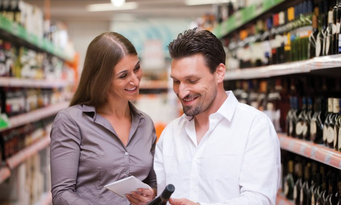 Happy young couple smiling while shopping for wine together at supermarket