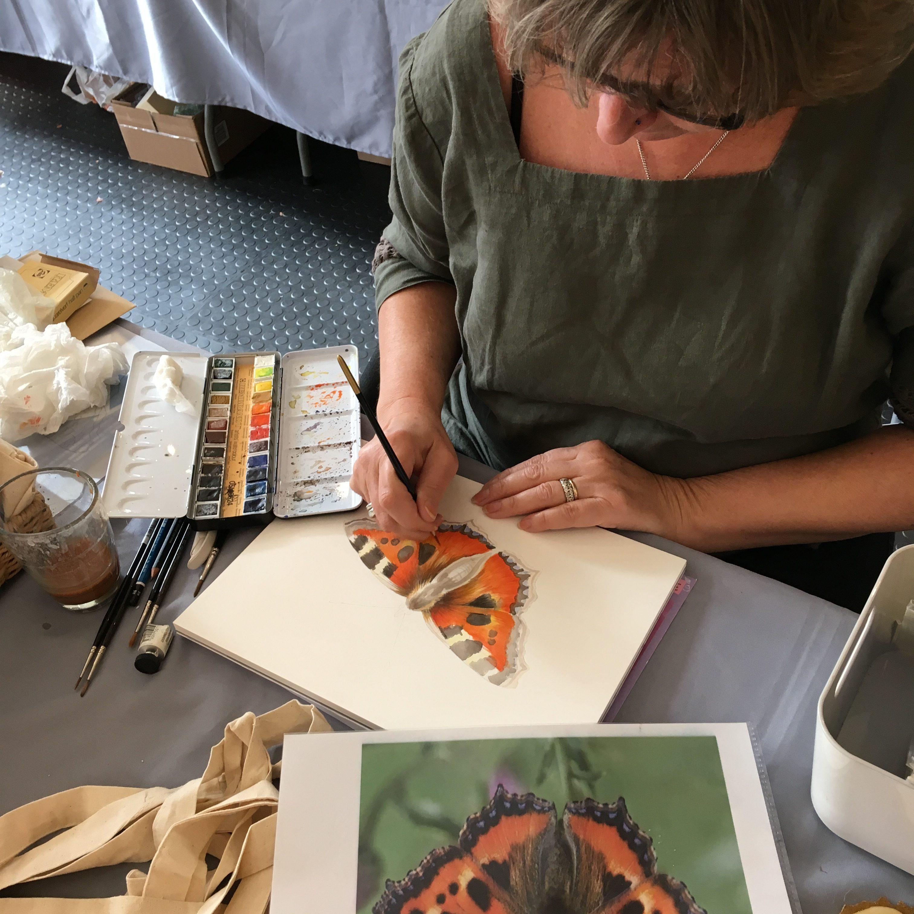 Artist painting Tortoiseshelll butterfly in watercolour