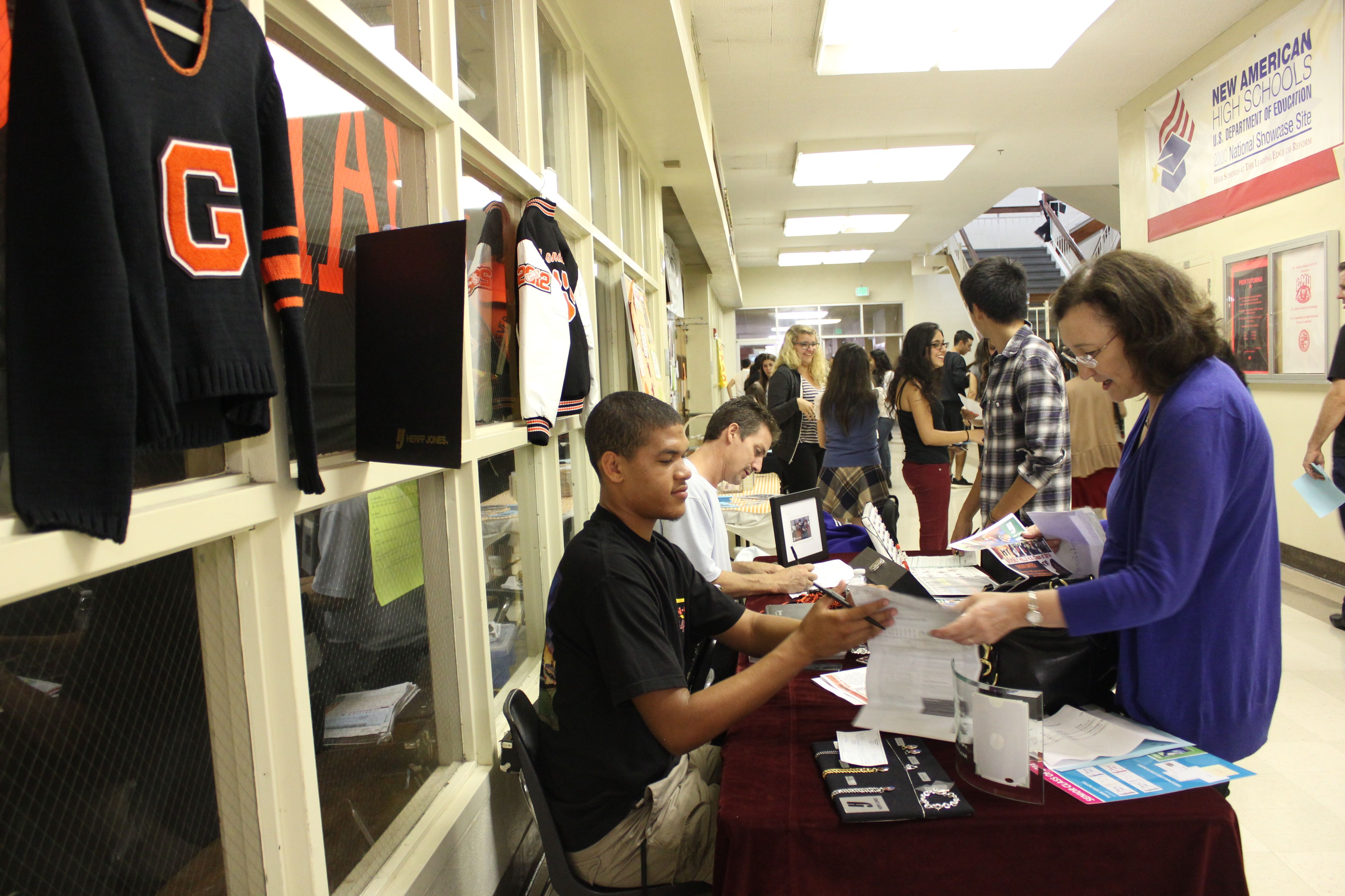 Herff Jones explains pricing details to parents at Back To School Night's booth.
