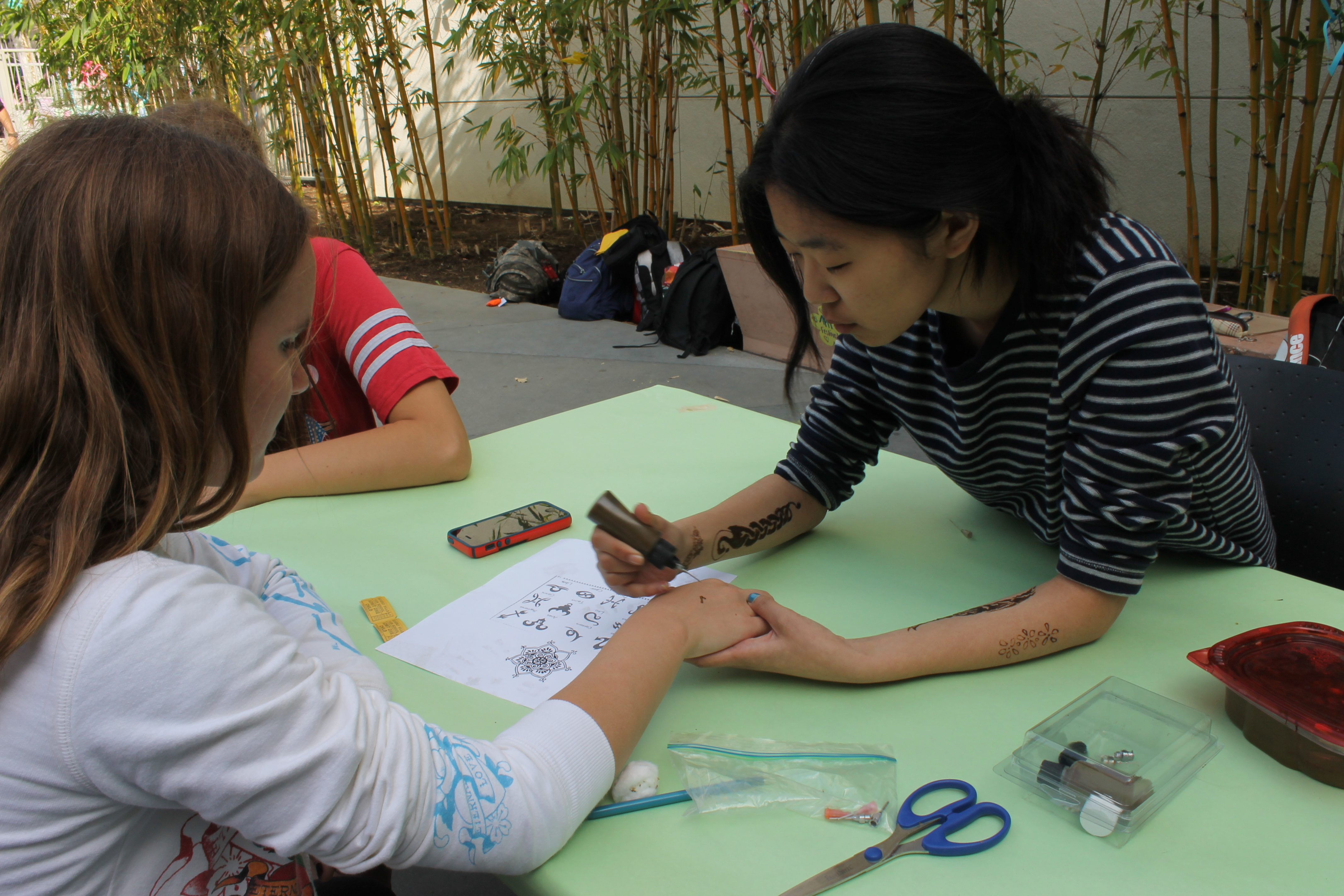 Senior Annette Chang gives a henna tattoo to an attendee.