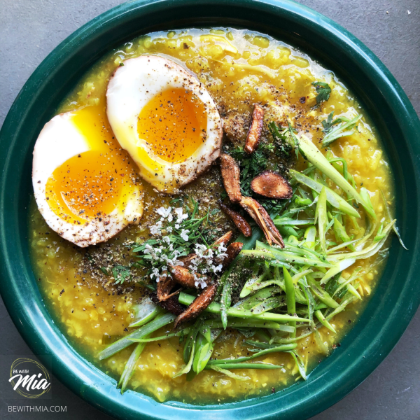 Turmeric Arroz Caldo topped with spring onions, crispy garlic, cilantro blooms and boiled eggs