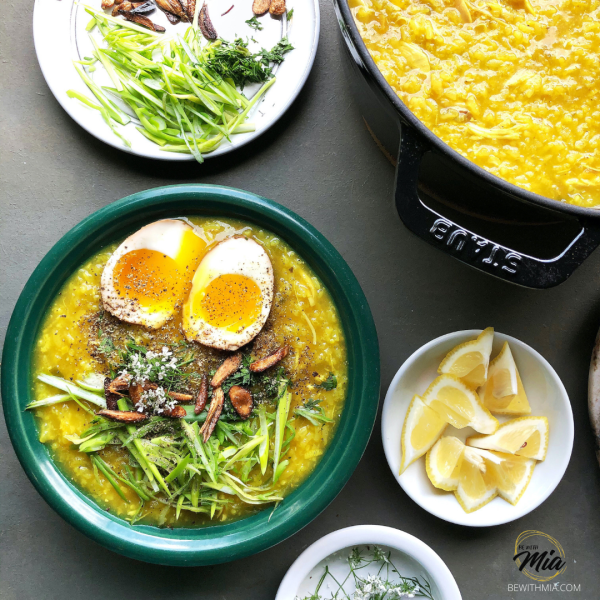 Turmeric Arroz Caldo topped with spring onions, crispy garlic, cilantro blooms and boiled eggs and lcitrus