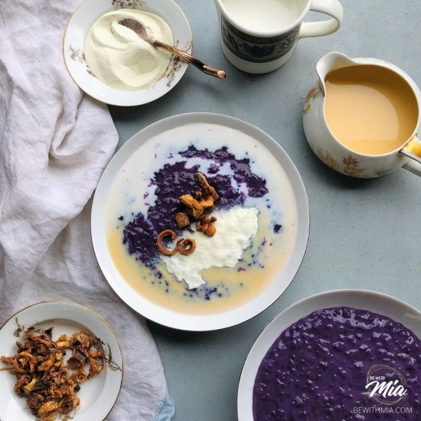 A vibrant and delicious bowl of ube champorado served with three types of milk and crispy curled squid.