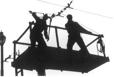 Silhouette workman cutting trolley wires on tower wagon