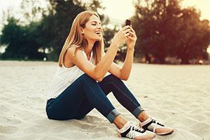 Beautiful woman on beach texting - main