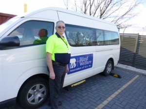 Volunteer driver standing at the side of the BWA Bus