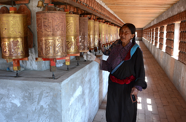 Two Monguor mothers spinning Buddhist prayer wheels on the ground floor. Rebkong, Amdo, Tibet
