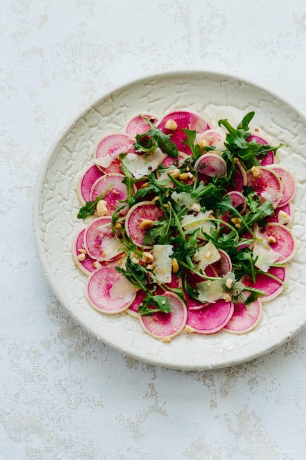 plate of watermelon radish carpaccio and arugula salad on white surface