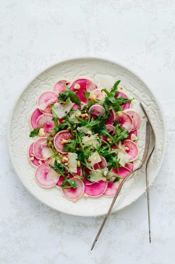 watermelon radish arugula salad on plate with forks