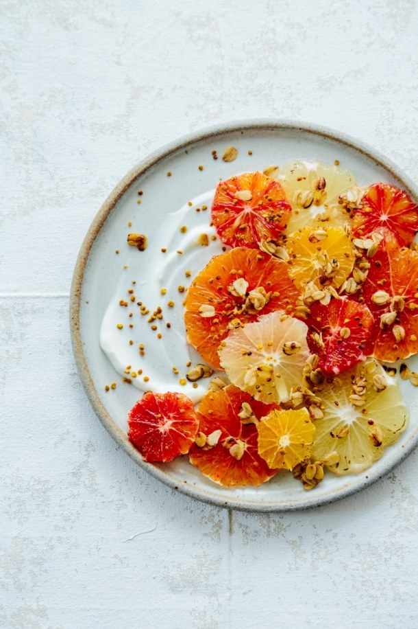 a plate of caramelized orange and grapefruit slices with yogurt oats and bee pollen