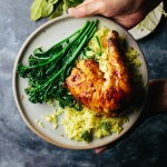hands holding a plate of roast lemongrass chicken and turmeric coconut rice