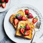 plate with two slices of French toast, strawberries, and fork