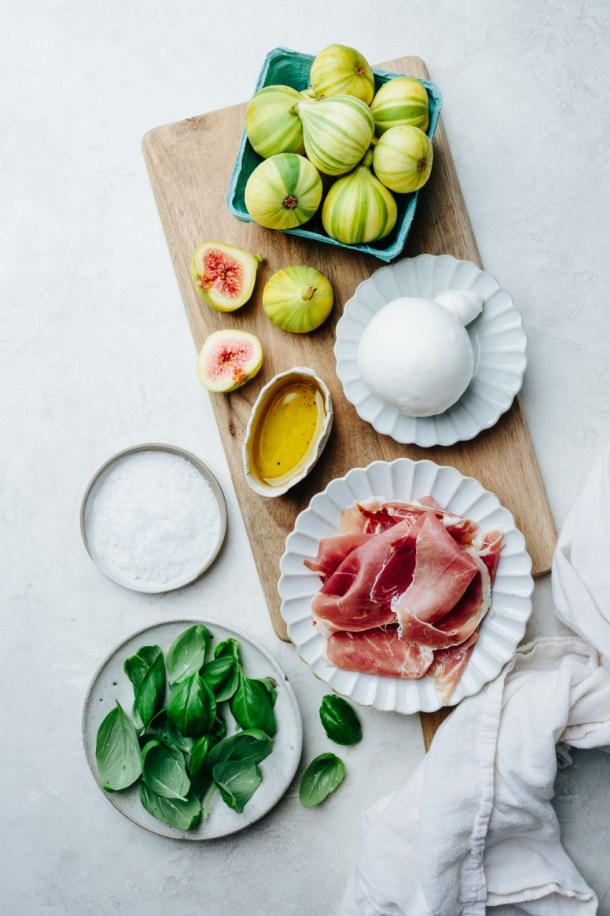 salad ingredients with basket of figs, plates of burrata, prosciutto, basil leaves, sea salt, and olive oil