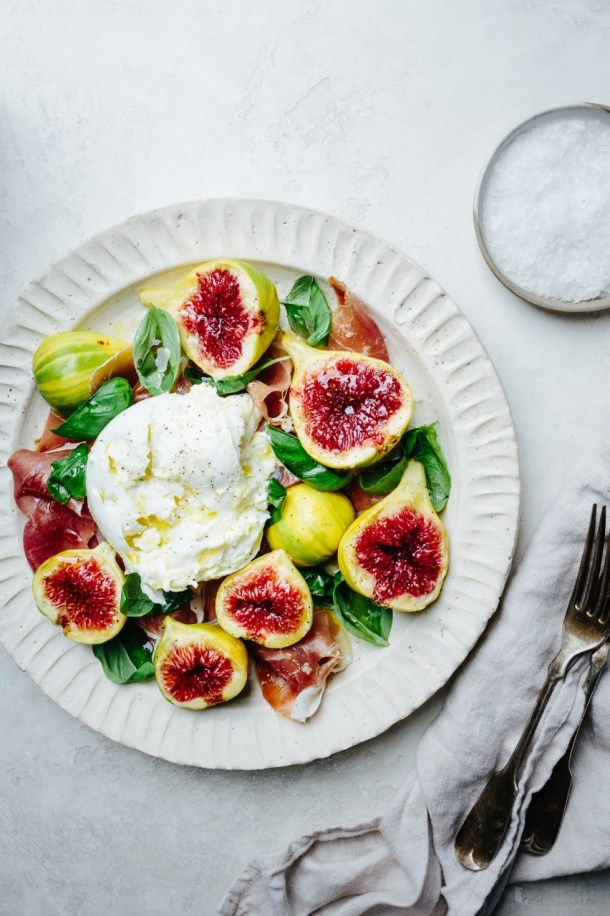 a plate of salad with fig, burrata, prosciutto, and basil leaves with two forks, linen, and a plate of sea salt