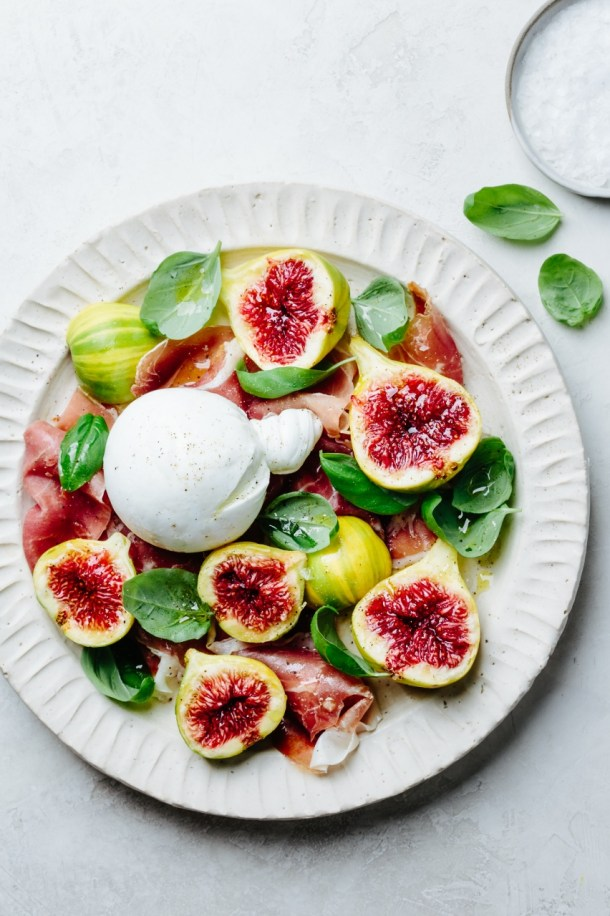 a plate of salad with fig, burrata, prosciutto, and basil leaves