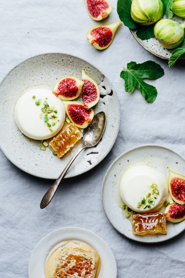 a plate of figs, a plate of honey comb, and two plates of orange blossom panna cotta