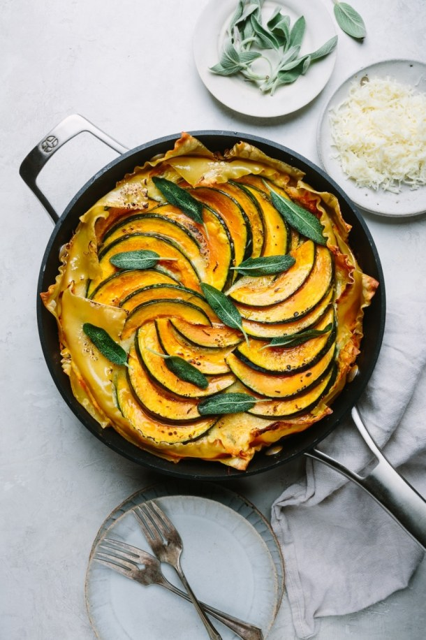 a skillet of baked pumpkin ricotta lasagna with two serving plates and fork, plate of cheese, and plate of sage leaves