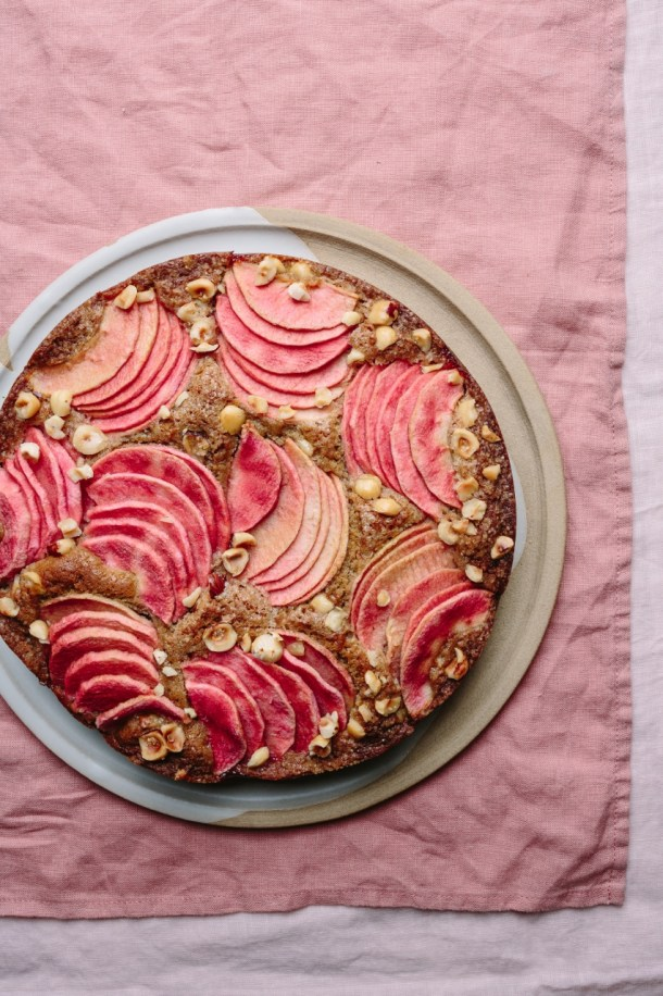 baked apple cake on platter with kitchen linens