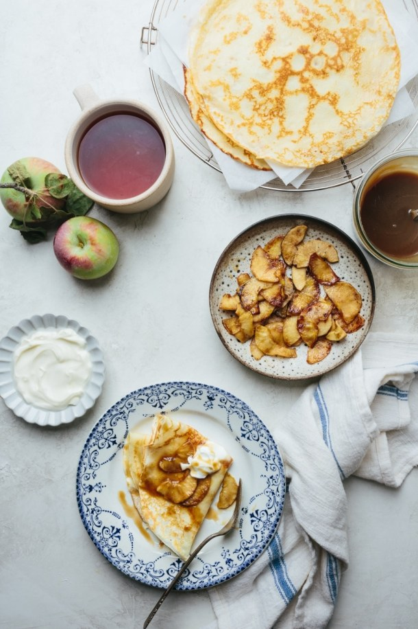 a plate of salted caramel crepes with stack of crepes on cooling rack, two apples, a plate of creme fraiche, a bowl of sauteed apples, and a jar of salted caramel