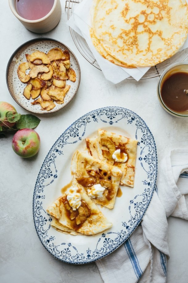 a plate of salted caramel crepes with two apples, a plate of creme fraiche, a bowl of sauteed apples, and a jar of salted caramel