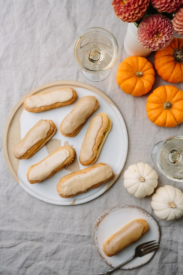 a large plate of salted caramel pumpkin eclairs, a small plate with an elcair and fork, with fresh flowers, mini pumpkins, and two glasses of wine