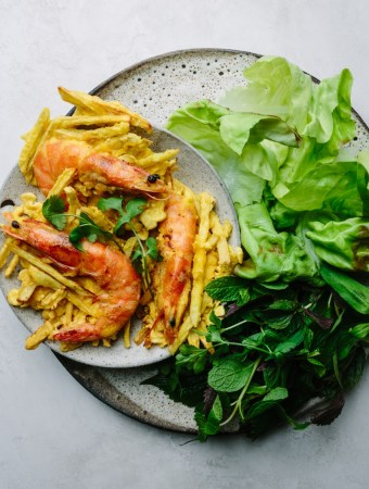 a plate of Vietnamese prawn and sweet potato fritters with fresh herbs