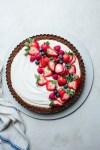 a berry yogurt tart on a platter next to a kitchen linen