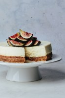 Instant Pot goat cheesecake on a cake stand with fresh figs and honey