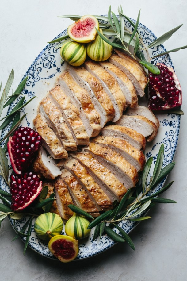 platter of sliced turkey breast garnished with fresh figs, pomegranates, and olive leaves