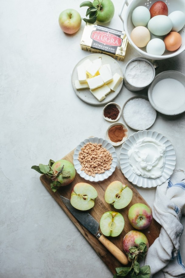 ingredients for toffee apple cake with cut apples on cutting board and knife, plate of toffee pieces, plate of yogurt, plates of salt, spices, sugar, butter, flour, and eggs