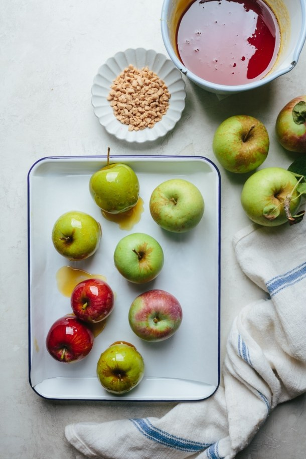 ingredients for toffee apples with fresh apples in a try, pan of toffee, plate of toffee pieces, and a kitchen towel