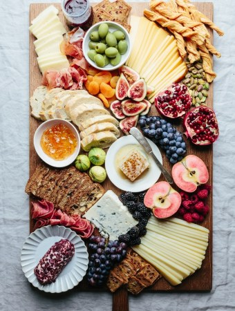 holiday cheese board with seasonal fruits, crackers, baguette, jam, olives