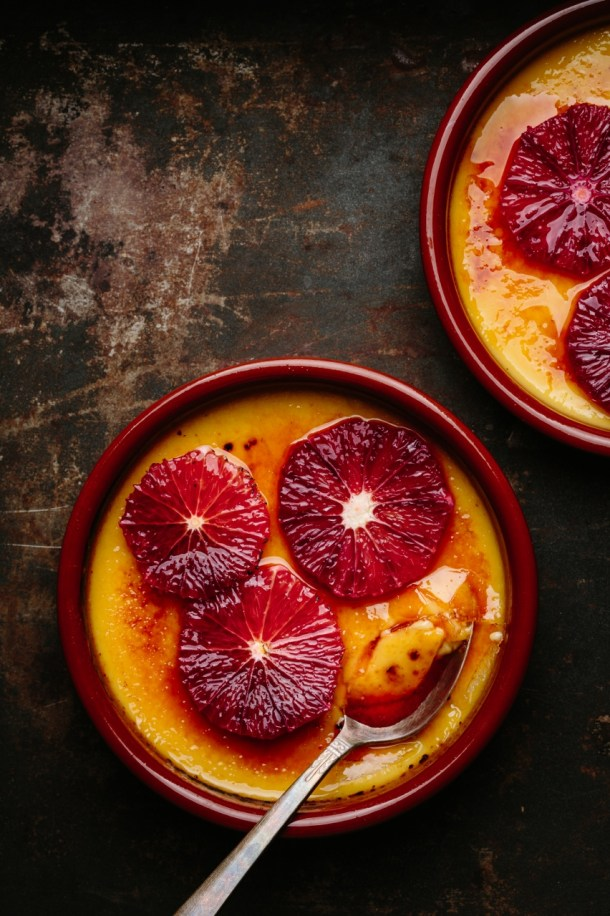 creme brulee topped with blood orange slices in ramekins with spoon