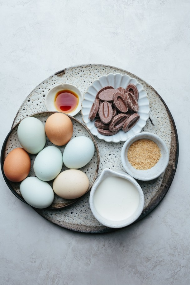 a platter with eggs, vanilla extract, chocolate pieces, sugar, and heavy cream