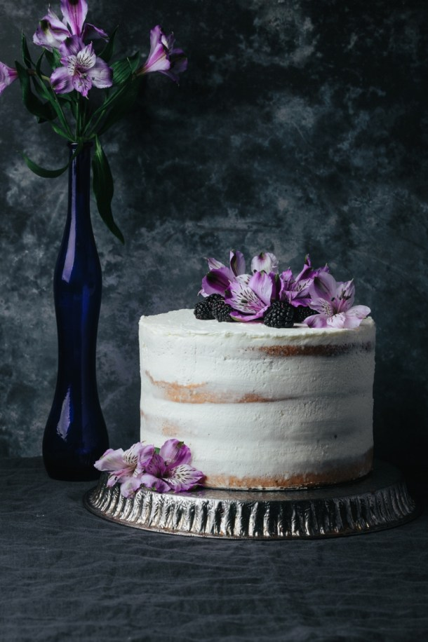blackberry Earl Grey cake on a metal stand next to a blue vase with flower