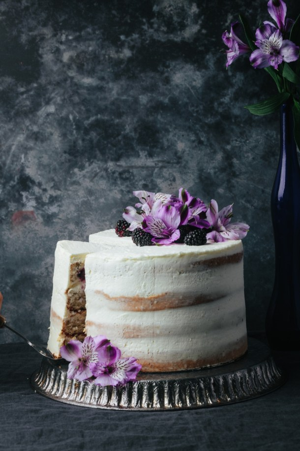 blackberry Earl Grey cake on a metal stand next to a blue vase with flower. Hand is removing a slice of cake.