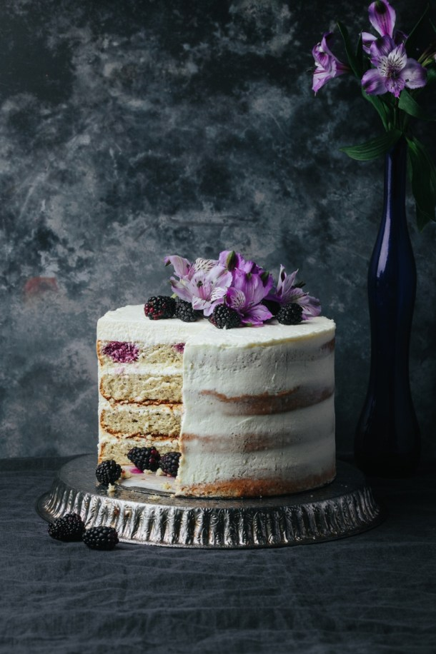 cut blackberry Earl Grey cake on a metal stand next to a blue vase with flower