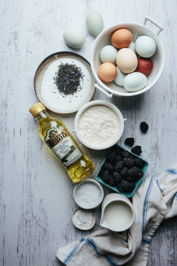 ingredients for cake, a basket of eggs with two eggs outside, a bowl of Earl grey tea leaves and sugar, a jar of flour, an olive oil bottle, a basket of blackberries, of bowl of salt, a bowl of baking powder, a cup of milk next to a kitchen linen