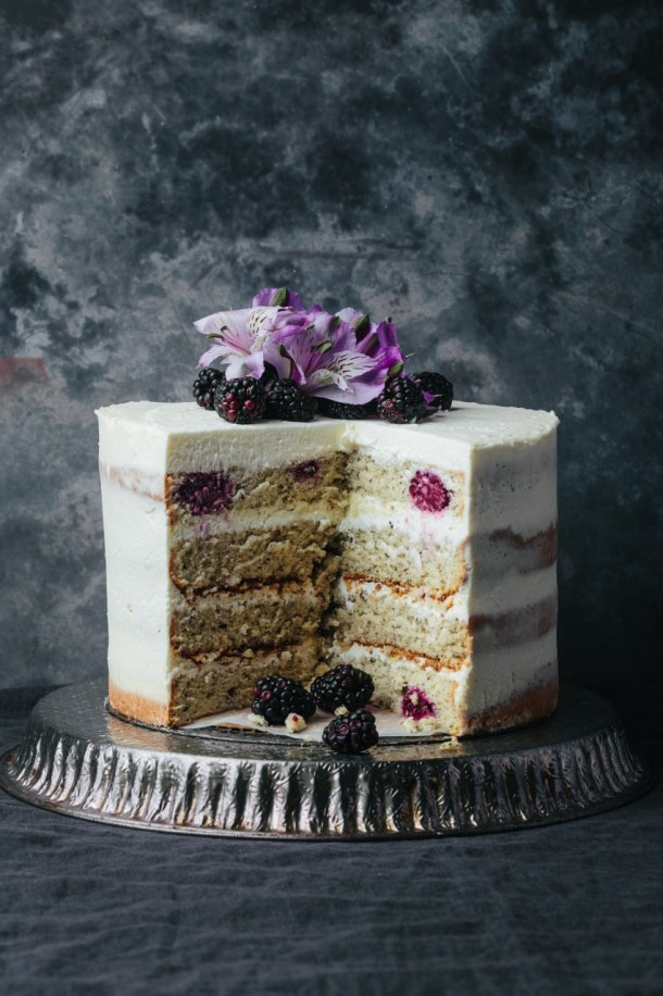 cut blackberry Earl Grey cake on a metal stand showing 4 layers