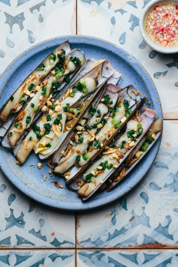 a plate of grilled razor clams topped with scallion oil, fried shallots, and roasted peanuts next to a bowl of dipping sauce