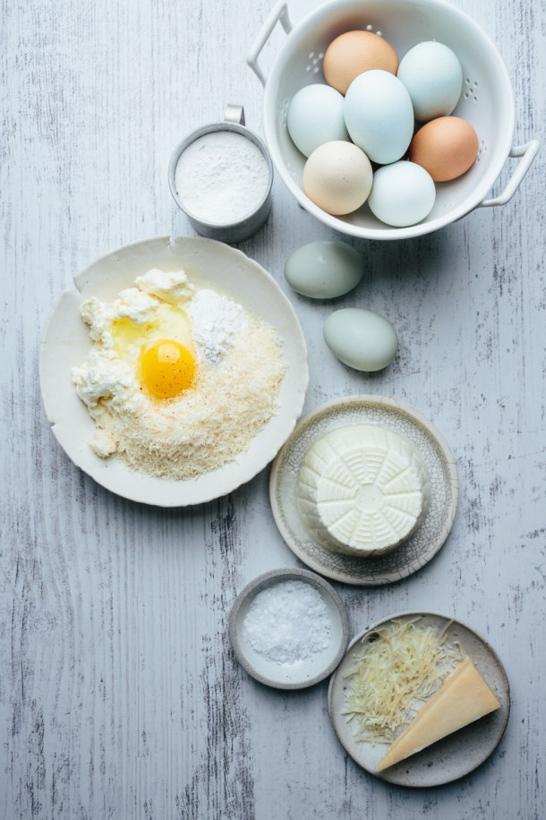 ingredients for ricotta gnudi, a palte of cheese, a bowl of salt, a plate of ricotta cheese, a bowl with cheese flour eggs, a basket of eggs, and a cup of flour