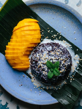 a plate of sliced mango with black sticky rice smothered in coconut sauce