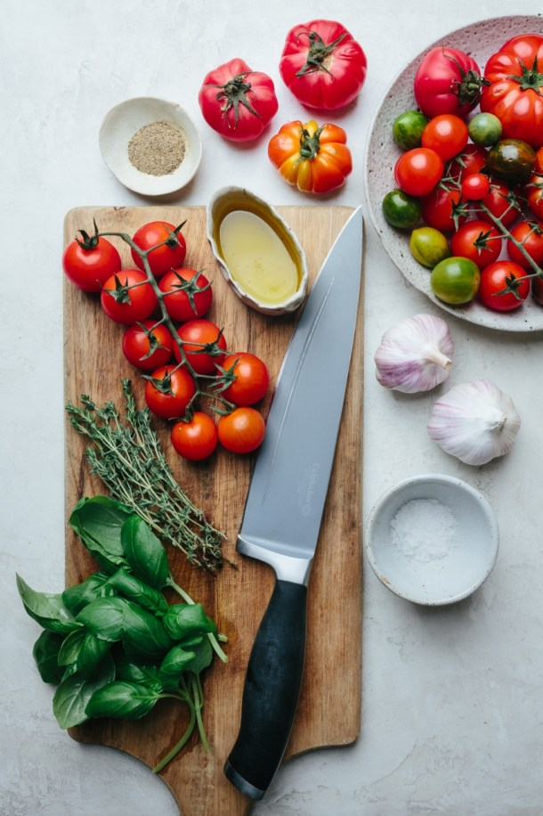 a bowl of olive oil, tomatoes, thyme sprigs, and basil leaves on a chopping board next to a knife, next to fresh tomatoes and a bowl of tomatoes, 2 heads of garlic, and a bowl of salt