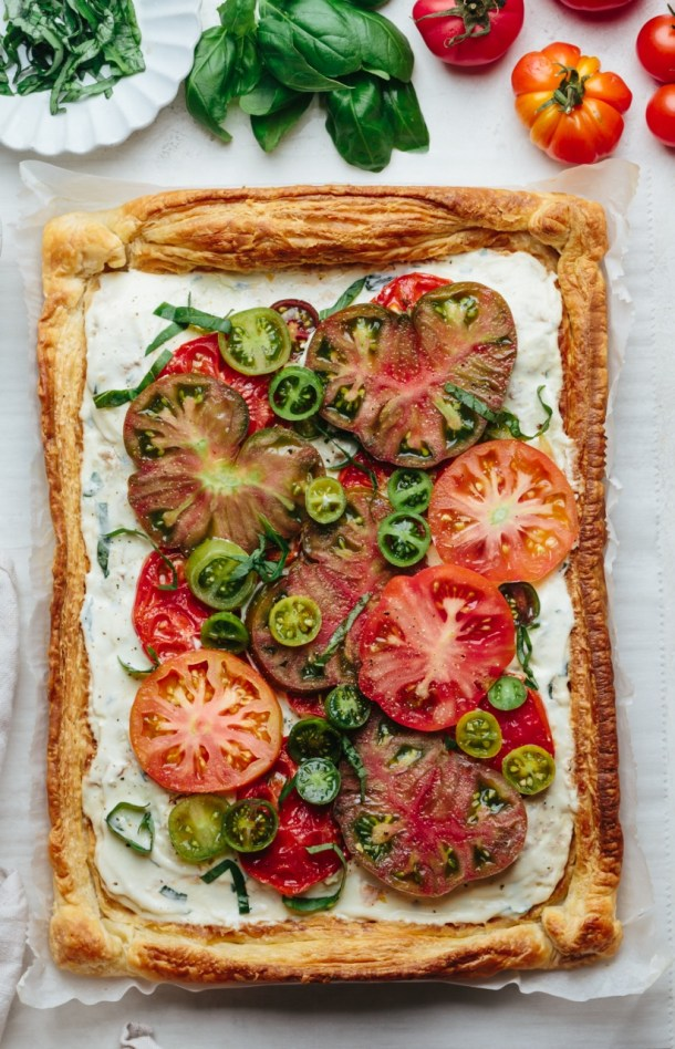 baked tomato tart on parchment paper next to fresh heirloom tomatoes, basil leaves, and a bowl with cut basil leaves