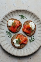 a plate of three buckwheat blini topped with smoked salmon, creme fraiche, and dill